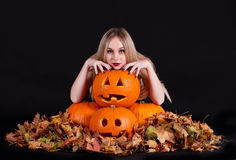 Charming halloween witch with funny pumpkins and leaves Stock Photos