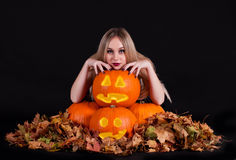 Charming halloween witch with glowing funny pumpkins and leaves Stock Photo