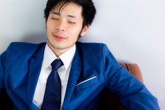 Charming handsome businessman is napping for while on sofa at of royalty free stock photos