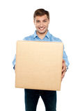 Charming handsome male holding carton Royalty Free Stock Images