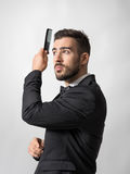 Charming handsome young man combing hair looking up Stock Photos