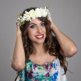 Charming happy beauty holding floral tiara and smiling at camera Stock Images
