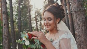Charming and happy bride in a beautiful wedding dress with a bouquet of flowers in a pine forest in the sun. Wedding day stock video footage