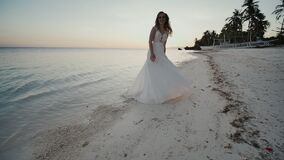 Charming and happy bride in a white dress dancing barefoot on the sandy shore of a tropical beach. Ocean. The palms. Sunset stock video