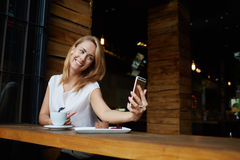 Charming happy hipster girl photographing herself on cell telephone camera while relaxing in modern coffee shop, Royalty Free Stock Images