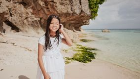 A charming and happy philippine teenage girl in a white summer dress is running along a tropical beach near the rocks. She is happily spinning. Childhood stock footage