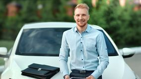 Charming happy positive young business man posing outdoor looking at camera sitting on car bonnet. Medium shot. Portrait of adorable laughing fashion male stock footage