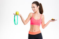 Charming happy young sportswoman choosing between healthy and unhealthy food Royalty Free Stock Photography
