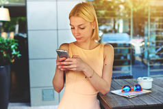 Charming hipster girl chatting on cell phone standing at coffee shop Stock Photo
