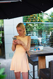 Charming hipster girl chatting on cell phone standing at coffee shop Royalty Free Stock Photo