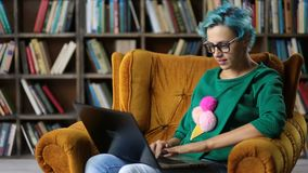 Charming hipster girl typing on laptop in library stock footage