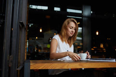 Charming hipster girl waiting for her friends in coffee shop, attractive woman thinking about something while sitting in bar Stock Image