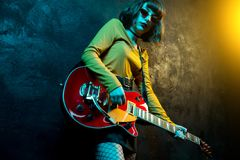 Charming hipster woman with curly hair with red guitar in neon lights. Rock musician is playing electrical guitar. 90s. Style concept royalty free stock photography