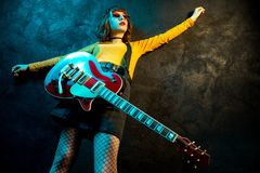 Charming hipster woman with curly hair with red guitar in neon lights. Rock musician is playing electrical guitar. 90s. Style concept royalty free stock photos