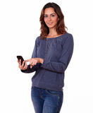 Charming hispanic female texting on cellphone. Portrait of a charming hispanic female texting on cellphone while standing on white background Royalty Free Stock Photo