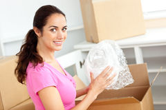 Charming hispanic woman unpacking boxes of glasses Royalty Free Stock Photo