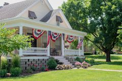 Charming home decorated with American flags for the Fourth of July. Charming home with cozy front portch decorated with American flags for the Fourth of July stock image