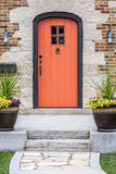 Charming home with orange front door and stone entrance Stock Photography