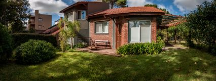 Charming home with red bricks cozy house and front garden at a residential neighborhood royalty free stock photo