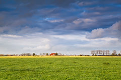 Charming house on farmland at storm Stock Image