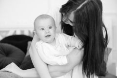 Charming infant girl in mother arms indoors. royalty free stock photos