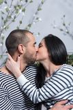 Charming international couple in striped sweaters kissing and hu Stock Photography
