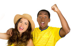 Charming interracial couple wearing yellow football shirts cheering joyfully to camera, white studio background Royalty Free Stock Photos