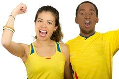 Charming interracial couple wearing yellow football shirts cheering joyfully to camera, white studio background Royalty Free Stock Image