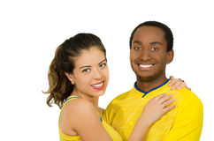 Charming interracial couple wearing yellow football shirts, embracing friendly while posing for camera, white studio Royalty Free Stock Image