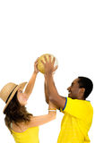 Charming interracial couple wearing yellow football shirts holding ball up in air between each other, profile angle Royalty Free Stock Photos