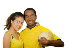 Charming interracial couple wearing yellow football shirts, hugging friendly while posing for camera holding ball, white Royalty Free Stock Photography