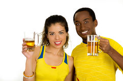 Charming interracial couple wearing yellow football shirts, posing for camera holding beer glasses and smiling, white Royalty Free Stock Image