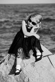 Charming joyful little girl in a summer black dress dreaming and smiling at the beach on the rock Royalty Free Stock Image