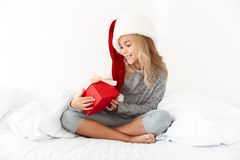 Charming kid girl in Santa`s hat looking at her gift box while s Royalty Free Stock Images