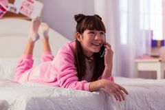 Charming kid having pleasant conversation per telephone. Relaxed atmosphere. Cute brunette girl expressing positivity while communicating with her friend stock photos