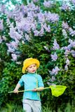 A charming kid playing with a scoop on a meadow in a warm and sunny summer or spring day. Active rest for children. A boy boy is fun with pleasure for stock images