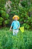 A charming kid playing with a scoop on a meadow in a warm and sunny summer or spring day. Active rest for children. A boy boy is fun with pleasure for stock image