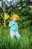 A charming kid playing with a scoop on a meadow in a warm and sunny summer or spring day. Active rest for children. A boy boy is fun with pleasure for royalty free stock photo