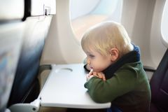 Afraid little boy sitting by aircraft window during the flight. Charming kid traveling by an airplane. Afraid little boy sitting by aircraft window during the Royalty Free Stock Photography