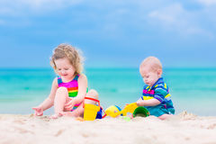 Charming kids playing on the beach Stock Images