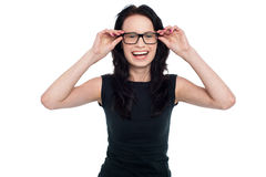 Charming lady adjusting her eyeglasses Royalty Free Stock Photography