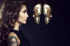 Charming lady with dark wavy silky hair wearing jewel crown and looking in the face of Venetian mask hanging in the air. Close up portrait of charming lady with Stock Images