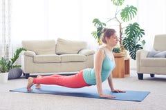 Charming lady doing upward-facing dog pose standing on yoga mat Stock Photo