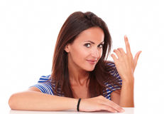 Charming lady with finger pointing up. And looking at camera in white background - copyspace royalty free stock image