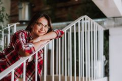 Charming lady in glasses leaning on stair railing royalty free stock image