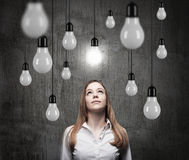 Charming lady is looking upward at the hanging light bulbs. A concept of searching new ideas. Dark concrete background royalty free stock images