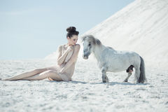 Charming lady playing with the pony Royalty Free Stock Image