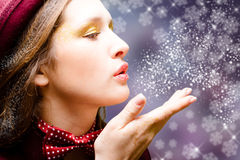 Charming lady with red bow tie blowing snowflakes Stock Images