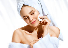 Charming lady removes makeup from her delicate skin of her face with a cotton swab. stock images