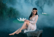 Charming lady, sitting on a huge rock in the middle of the lake. Royalty Free Stock Photography